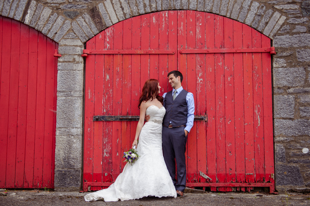 man and wife standing beside red barn door