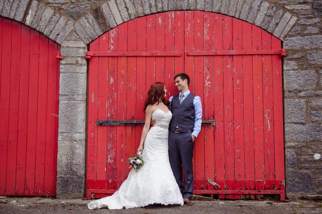 man and wife standing beside red barn door