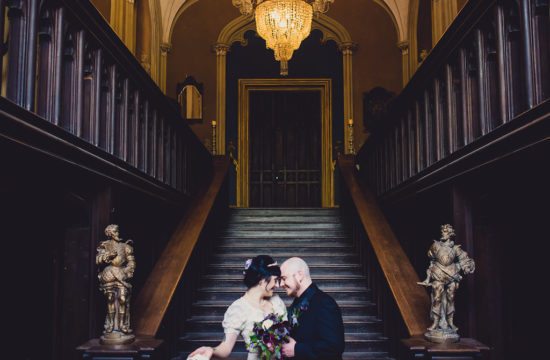 just married couple embracing in gothic castle bottom of stairs