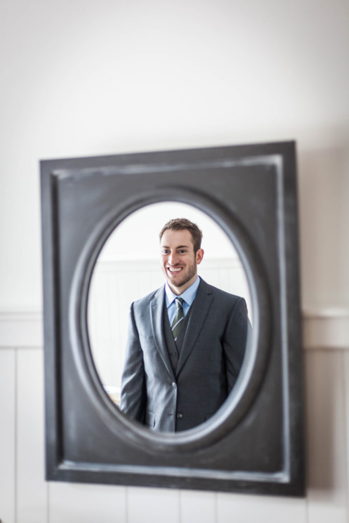 elope to ireland ballycarbery castle groom looking in the mirror