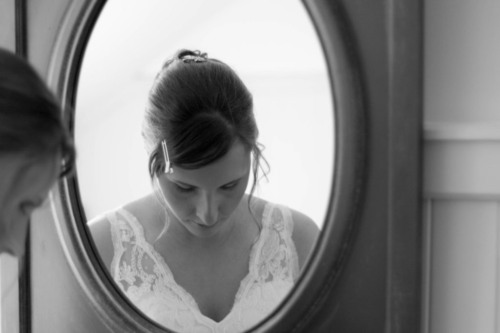 elope to ireland bride looking down whilst beside the mirror