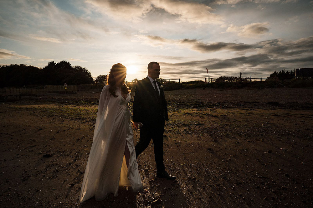 castle elopement bride and groom walking in the twilight